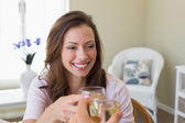 Smiling woman toasting wine glass at home — Stock Photo