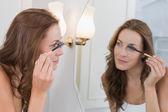 Side view of a beautiful young woman applying mascara — Stock Photo