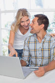 Cheerful couple doing online shopping at home — Stock Photo
