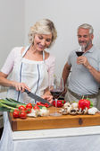 Man with wine glass and woman chopping vegetables in kitchen — Photo