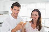 Loving couple toasting wine glasses in kitchen — Stock Photo