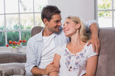 Relaxed loving young couple sitting on sofa — Stock Photo