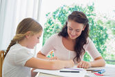 Mother assisting daughter in drawing — Stock Photo
