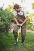 Young man in dungarees raking the garden — Stock Photo