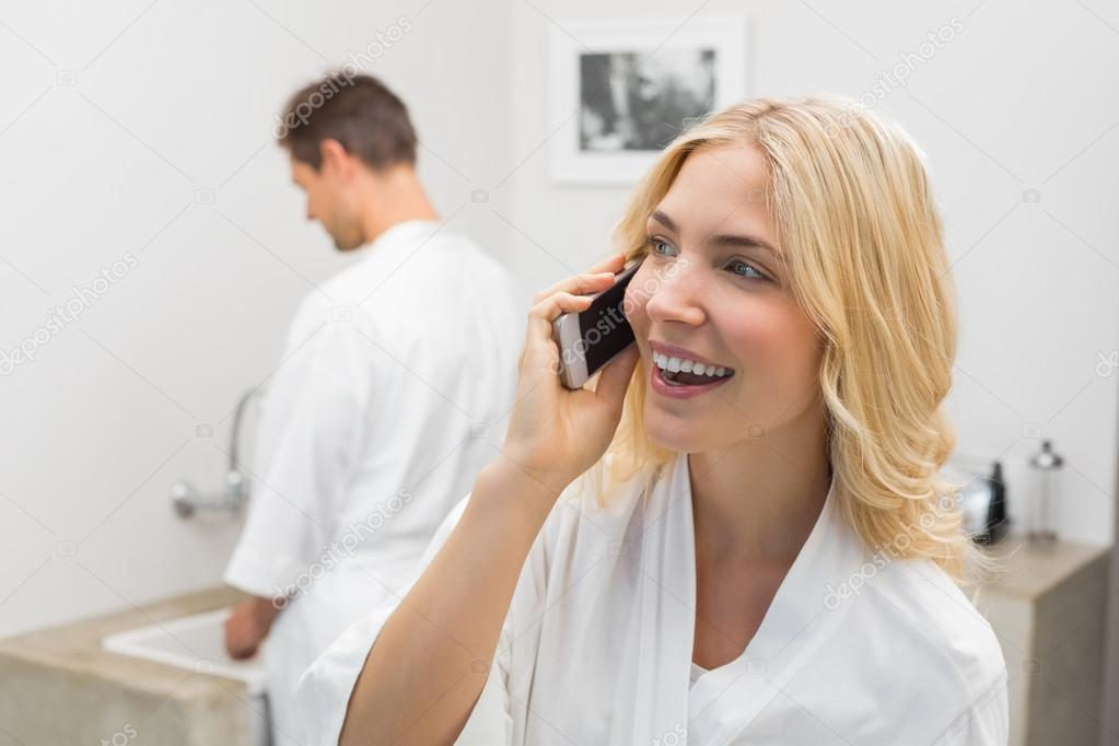 女人跟男人在厨房里的背景中使用手机