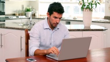 Handsome man using laptop at the table — Stok video