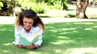 Happy woman lying on grass reading book — 图库视频影像