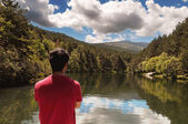 Man back observes the landscape reflected in the calm lake — Stock Photo