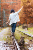 Woman and her pet walk the train tracks — Stok fotoğraf