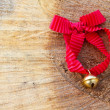 Jingle bell with red ribbon in the wood — Stock Photo