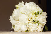 The beautiful white bouquet of flowers of bride in wedding with white peonys and freesia — Stock Photo