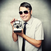 Funny guy wtih instant camera — Stock Photo