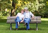 Starší pár sedící na lavičce v parku — Stock fotografie
