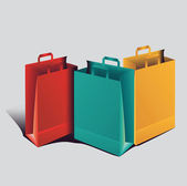 Three colored paper shopping bags — Stock Vector