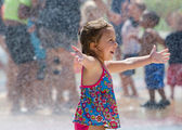 Happy little girl in a summer fountain — Stock Photo