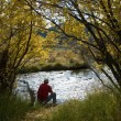 Man sitting and thinking beside a river — Stock Photo