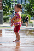Blissful child in fountain — Stock Photo
