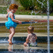 Toddler and baby brother play in summer fountain — Stock Photo #32932305
