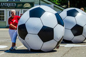 Woman rolling giant soccer ball — Stock Photo