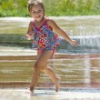 Happy girl dancing in a summer fountain — Stock Photo #33161433