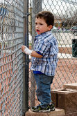Child looking thru fence — Stock Photo