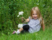 Little blond girl with flowers — Stock Photo