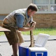 Man pulls snake out of a cooler — Stock Photo