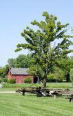 Rural  red barn with split rail fence — Stok fotoğraf