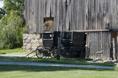 Old amish buggy outside a weathered barn — Stock Photo