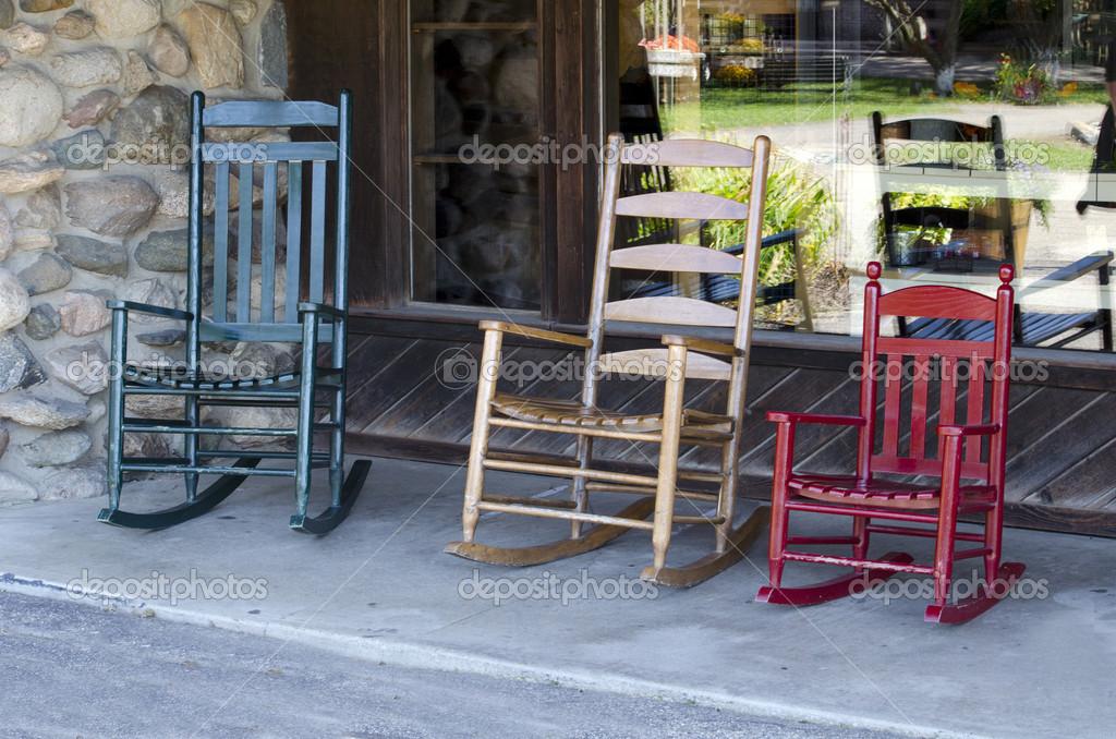 Tre sedie a dondolo in diversi colori su un portico foto for Piani portico di tre stagioni