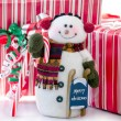 Stock Photo: Snowman with red and white packages and candy cane