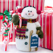 Snowman with red and white packages and candy cane — Stock Photo