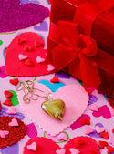 Zlaté srdce náhrdelník na růžové srdce s srdce zpět zem a červené krabičky — Stock fotografie