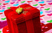 Red gift box with heart necklace on a heart back ground — Stock Photo