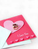 Wedding rings and a love card — Stock Photo