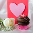 Valentine with chocolate frosted cupcake and a white rose — Stock Photo #40572569