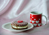 Whooppe pie and a red and white heart mug of coffee on pink silk — Stock Photo