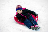 Child laughing as she sleds down a hill — Stock Photo