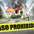 Stock Photo: Spanish Paso Prohibido tape with firefighters and burning hous