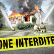 Stock Photo: French Zone Interdite tape with firefighters and burning house