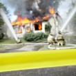 Empty  tape with firefighters and a burning house — Stock Photo