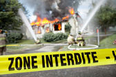 French Zone Interdite tape with firefighters and a burning house — Stock Photo
