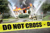 Do not cross tape with firefighters and a burning house — Stock Photo