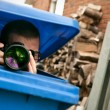 Paparazzi hiding in a blue garbage bin — Stock Photo