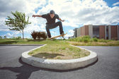 Skateboarder doing a Ollie Over a Grass Section — Zdjęcie stockowe
