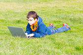 Child studying on the grass — Stock Photo