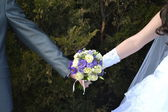 The bride and groom hold bouquet — Stock Photo