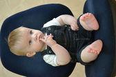 Der kleine junge sitzt auf einem blauen stuhl — Stockfoto