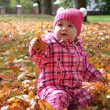 Little baby girl in autumn leaves holding a yellow balloon — Stock Photo #31779689
