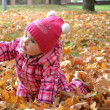 Little baby girl in autumn leaves holding a yellow balloon — Stock Photo